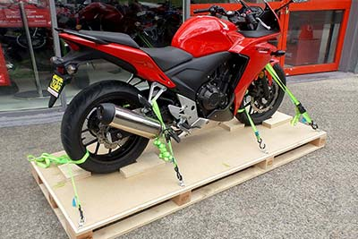 Motorbike securely strapped to base of packing crate